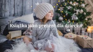 mała dziewczynka, pod choinką z prezentem dla dzieci i książką